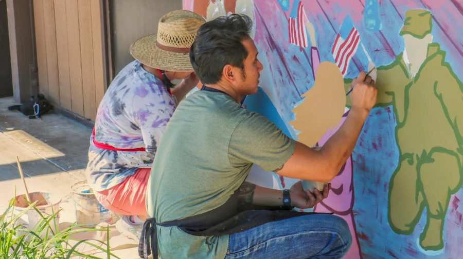 Students and faculty paint the Veteran's Mural by the Veteran's Resource Center at Foothill College