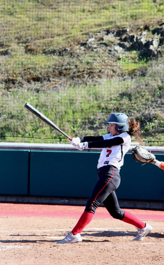 Tiana Bolin follows through a hard swing while at bat.