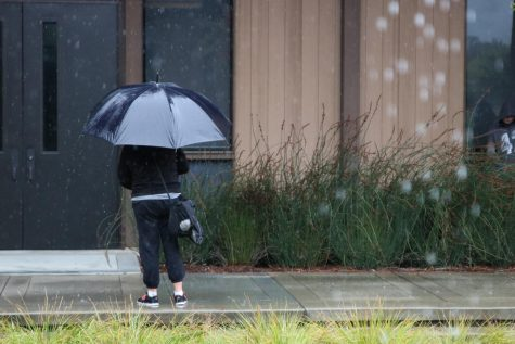 A student stands in the rain in front of a building at Foothill College.