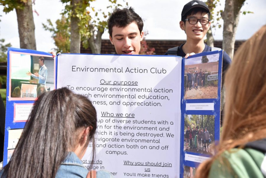 A+member+of+the+Environmental+Action+Club+tries+to+encourage+a+student+to+join+the+club.