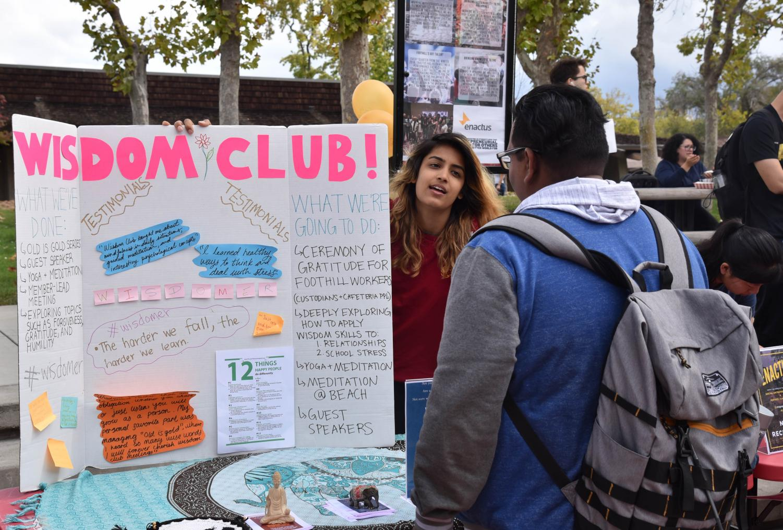 Pavini+Sethi+explains+the+purpose+of+Wisdom+Club+to+a+student.